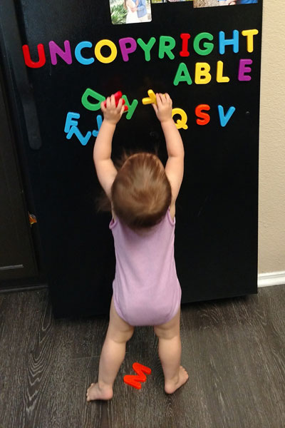 Toddler playing with alphabet letters on the fridge