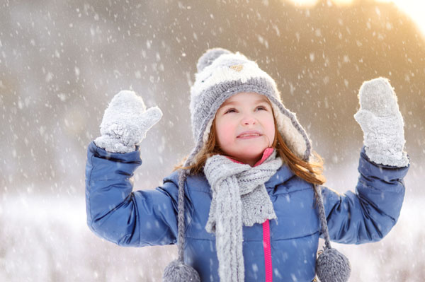girl playing in the snow during the holidays