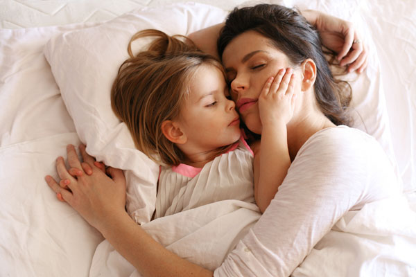 Mother and daughter cosleeping. It is possible to gently help a toddler sleep alone.