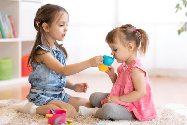 Two girls playing tea party - free play is an important part of homeschool preschool for this minimalist mom