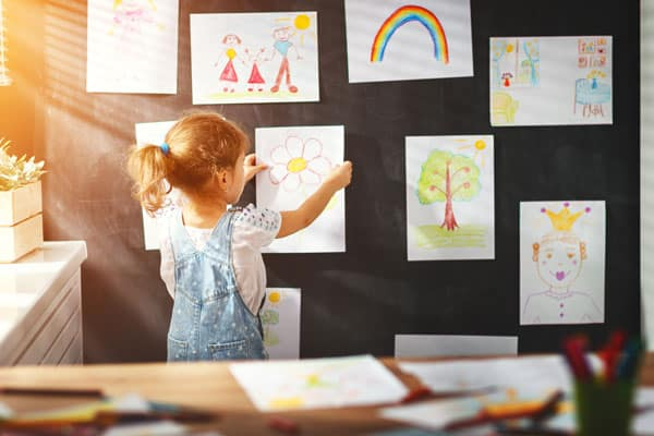 Preschooler displaying art projects - creativity is an important part of homeschool preschool