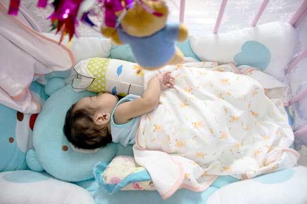 Baby in a crib with loose blankets, bumpers, and pillows. Crib sleeping is not inherently safe.